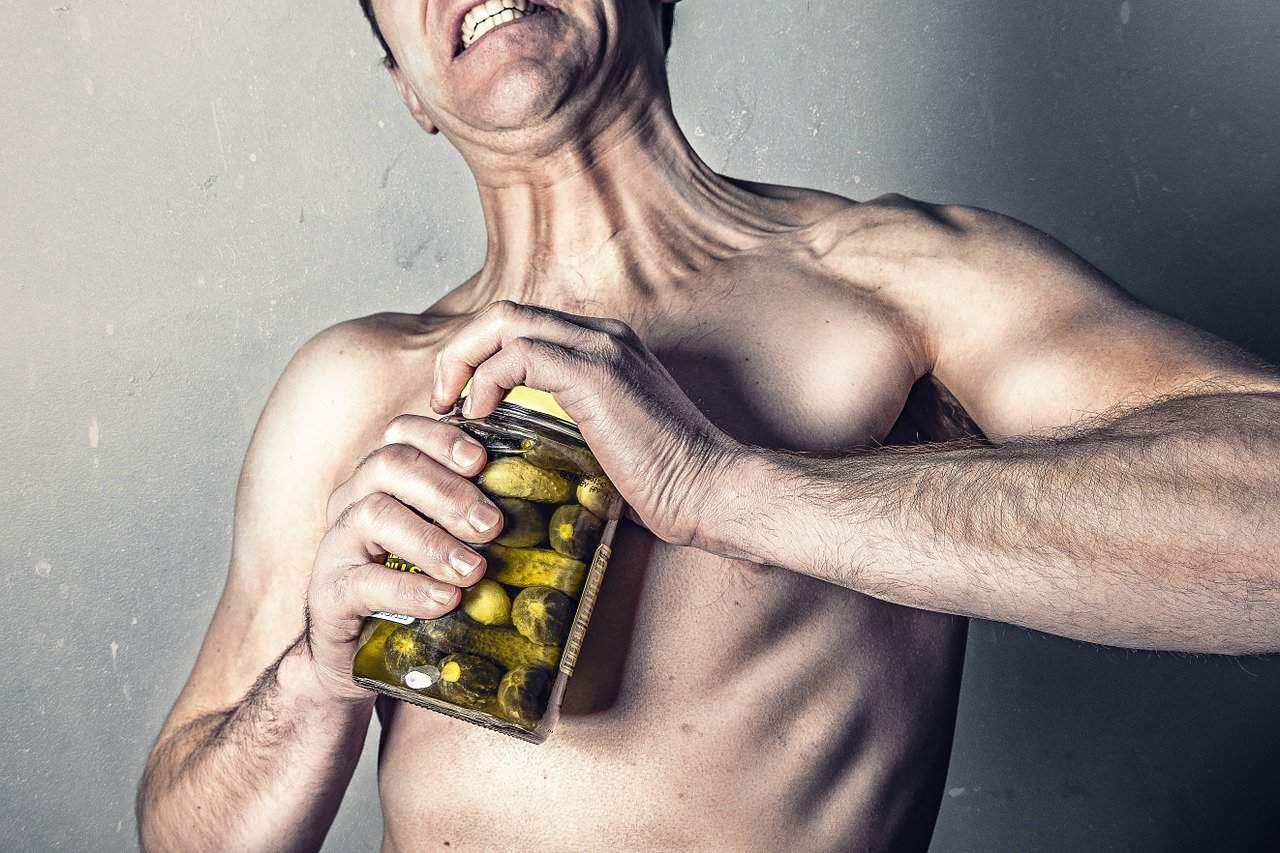 גבר בלי חולצה פותח צנצנת זיתים